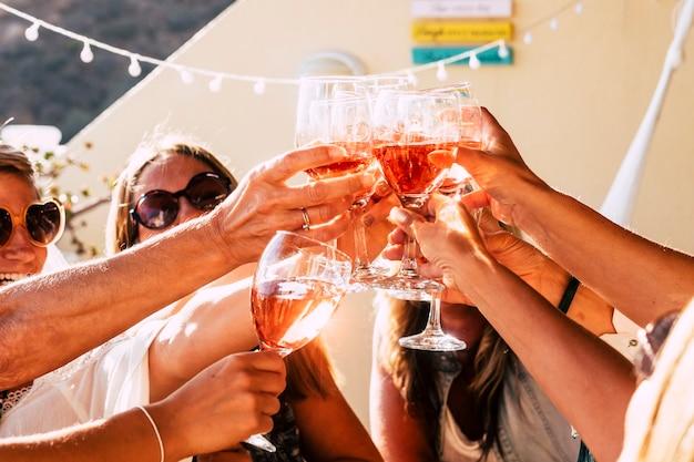 晴れた日に太陽の光の下で赤ワインのカップと一緒に乾杯する幸せな人々のグループ