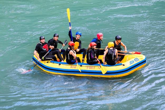 Группа счастливых людей с гидом рафтинг и гребля на реке.