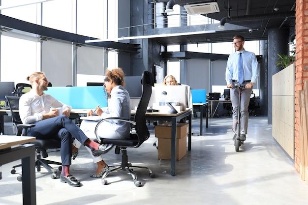 クリエイティブオフィスで一緒にスタートアップに取り組んでいる幸せな進歩的なビジネスマンのグループ。