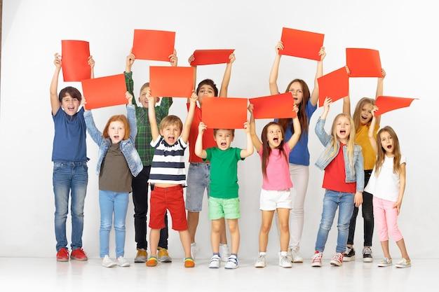흰색 스튜디오 배경에 격리된 빨간색 빈 배너를 들고 행복한 비명을 지르는 아이들. 교육 및 광고 개념입니다. 항의와 아동 권리 개념.