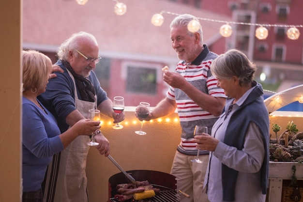幸せな先輩の友人のグループは、屋外テラスで自宅でバーベキューの夜を一緒に楽しんでいます