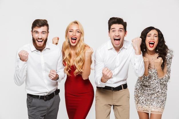 Группа счастливых умных одетых друзей, стоящих изолированно над белой, празднуя новый год