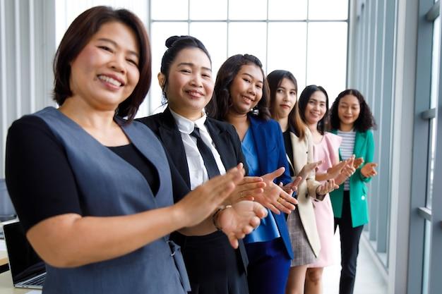 Группа счастливых улыбающихся женщин-офицеров в бизнесе носит стоячие овации бок о бок аплодируя руками, показывая теплое приветствие для продвижения по службе коллеги-менеджера в конференц-зале компании.