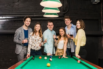 Group of happy smiling friends with drinks standing behind snooker table