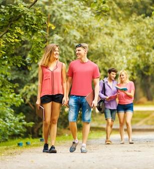 화창한 날 공원에서 행복한 학생들의 그룹이 도로에 있으며 교육에 대해 논의합니다.