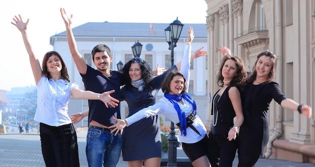 通りに立っている幸せな学生のグループ