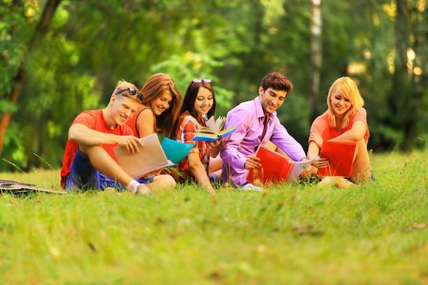 화창한 날 공원에서 책과 함께 행복한 학생들의 그룹