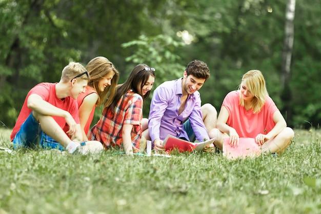 晴れた日に公園の本を持っている幸せな学生のグループ