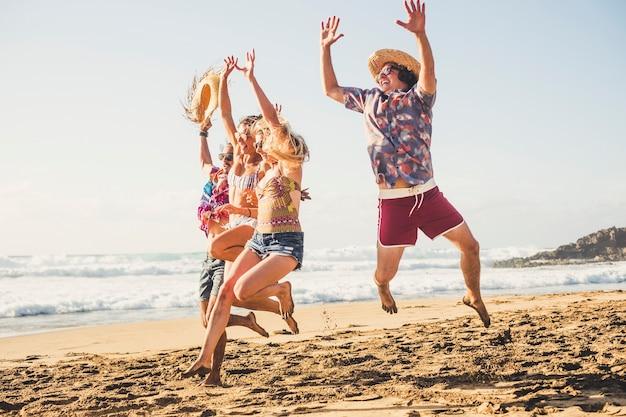 幸せな観光客のグループがビーチでジャンプ