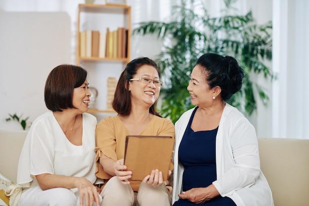 집에서 만날 때 재미있는 비디오를 보거나 태블릿 컴퓨터에서 사진을 보는 행복한 베트남 노인 여성 그룹