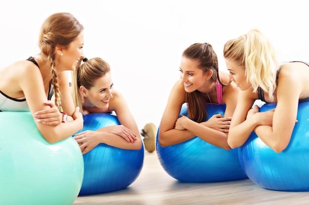 フィットボールでエアロビクスをしている幸せな女性のグループ