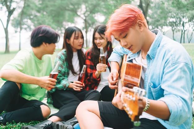 Группа счастливых молодых азиатов на пикнике в парке