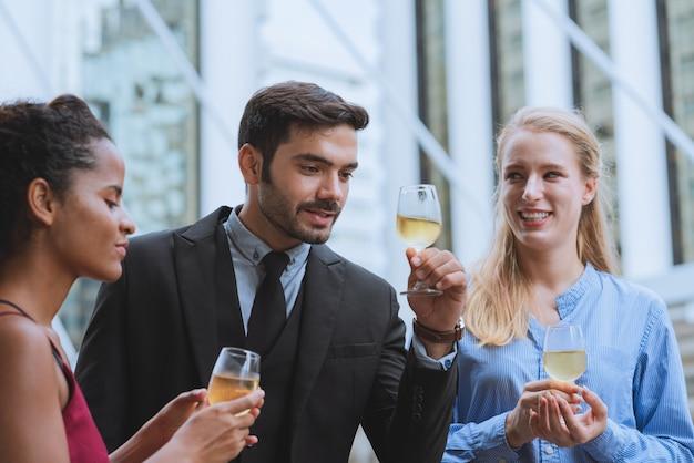 屋外で働くシャンパンのお祝いパーティーの成功を飲んで同僚と幸せな若いビジネスのグループ