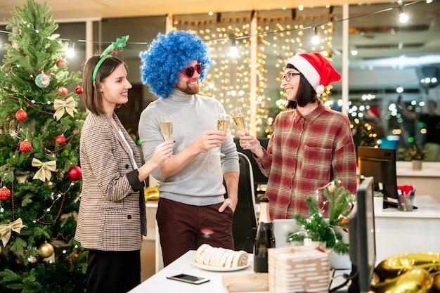Группа счастливых молодых бизнесменов, празднующих рождество в офисе и тостов с шампанским на празднике