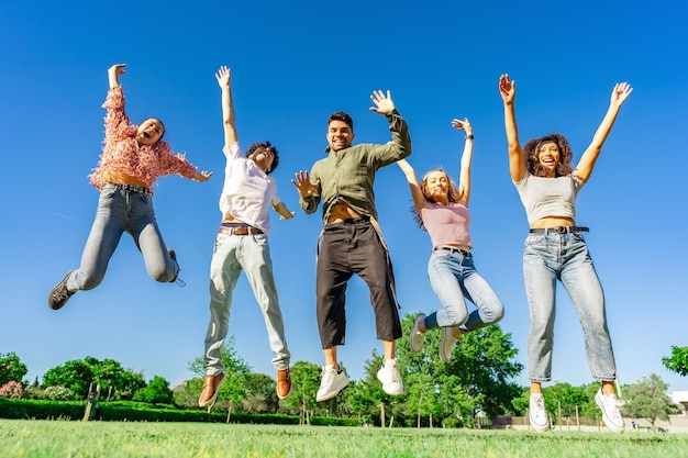 腕と脚を上げて一緒にジャンプする幸せな若い多様な多民族のz世代の友人のグループ