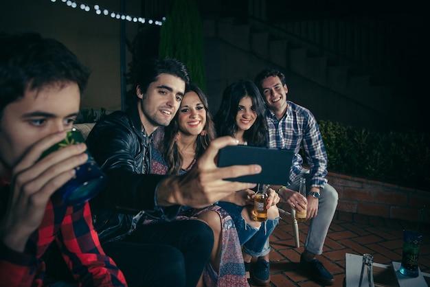 野外パーティーでスマートフォンで自分撮り写真を飲んで撮っている幸せな若い友人のグループ。友情とお祝いのコンセプト。