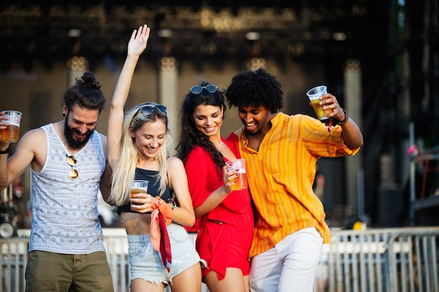 Группа счастливых молодых друзей, гуляющих и наслаждающихся напитками, фестиваль