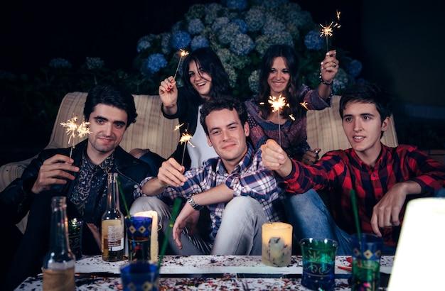 線香花火を持って野外パーティーで楽しんでいる幸せな若い友人のグループ。友情とお祝いのコンセプト。