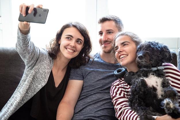 개를 껴안고 집에서 전화로 셀카를 찍는 행복한 젊은 친구들