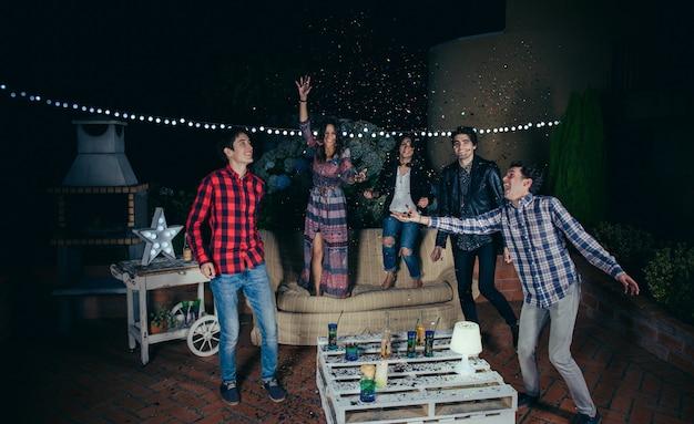 野外パーティーで色とりどりの紙吹雪の中で笑って楽しんでいる幸せな若い友人のグループ。友情とお祝いのコンセプト。