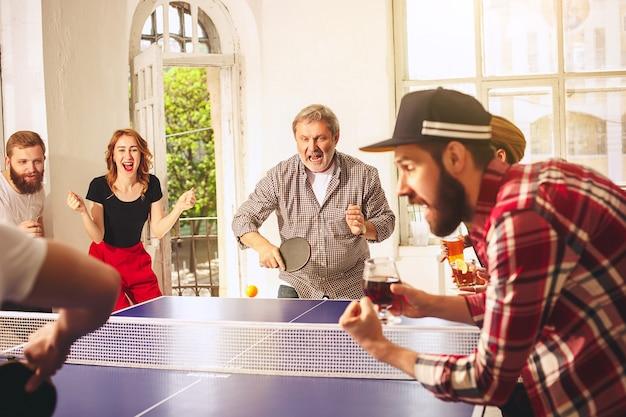 사무실이나 방에서 탁구 탁구를 치는 행복한 젊은 친구들. 건강한 스포츠와 진정한 감정의 개념. 라이프 스타일, 휴식 개념