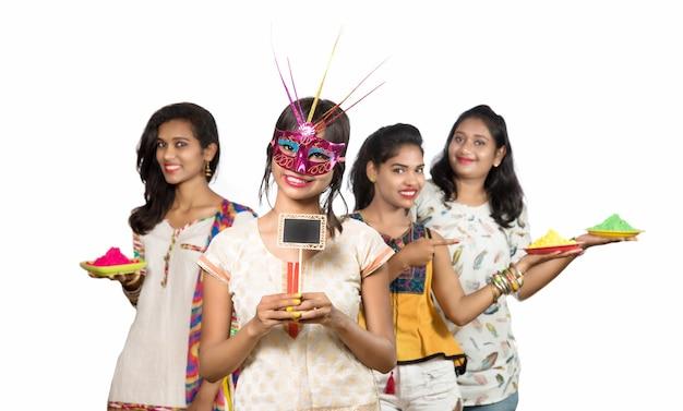 Группа счастливых молодых девушек, развлекающихся с красочной пудрой на фестивале красок холи