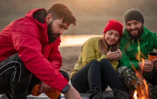 秋の夜に自然の中でトレッキングした後、焚き火の近くに座って、熱い飲み物を飲みながら、暖かいアクティブウェアで幸せな若いハイカーのグループ
