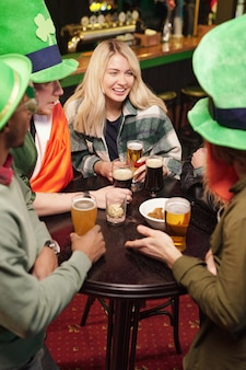 Группа счастливых молодых межкультурных друзей в зеленых шляпах и повседневной одежде, пьющих пиво с закусками за столом во время празднования дня святого патрика