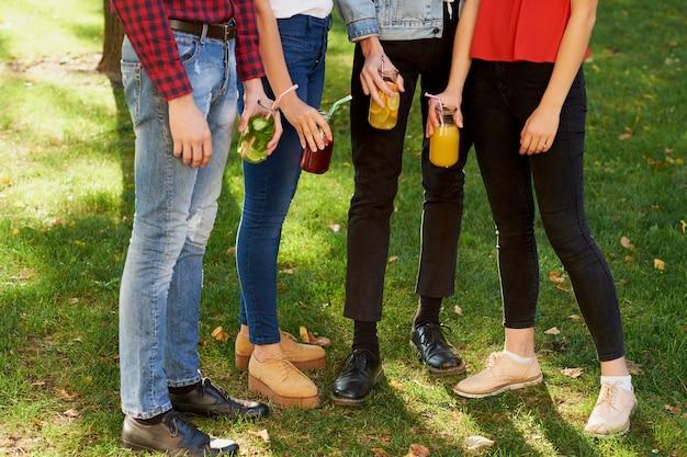 幸せな若者のグループは、デトックスカクテルを楽しんで、夏に一緒に時間を過ごします