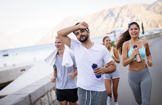 해변에서 야외에서 달리는 행복한 젊은 친구들
