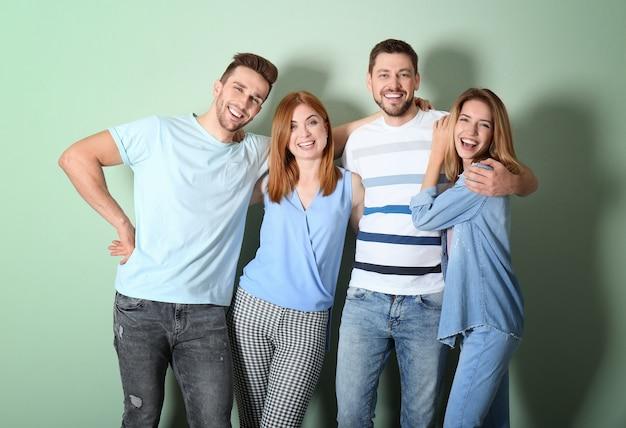Группа счастливых молодых людей на цветной поверхности