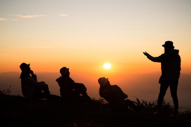 丘の上の幸せな若い人々のグループ。楽しんでいる若い女性