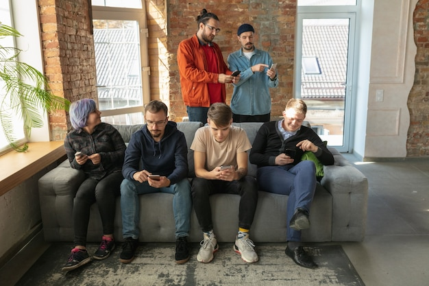 Группа счастливых молодых людей, делящихся в социальных сетях