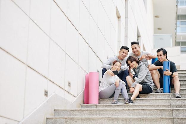 一緒にトレーニングした後、階段に座って自分撮りをしているヨガマットを持つ幸せな若いベトナム人のグループ