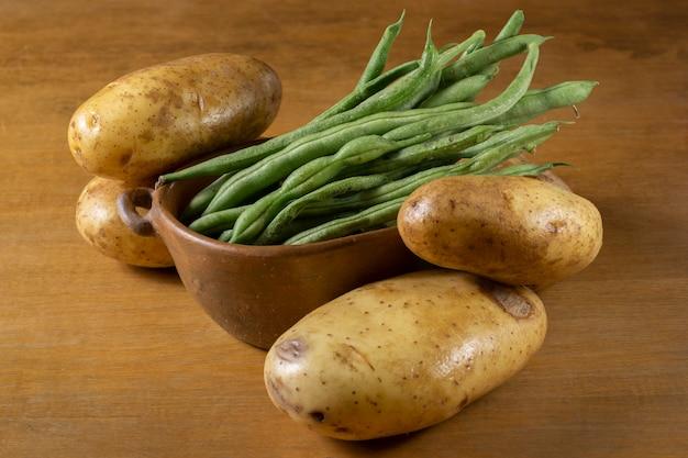 じゃがいもに囲まれた粘土ボウルのインゲン豆のグループ