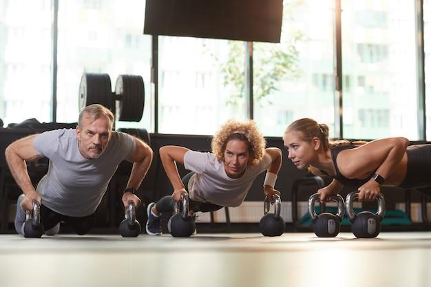 ジムでのトレーニング中に体操をしている床にダンベルを使ってトレーニングしている健康な人々のグループ