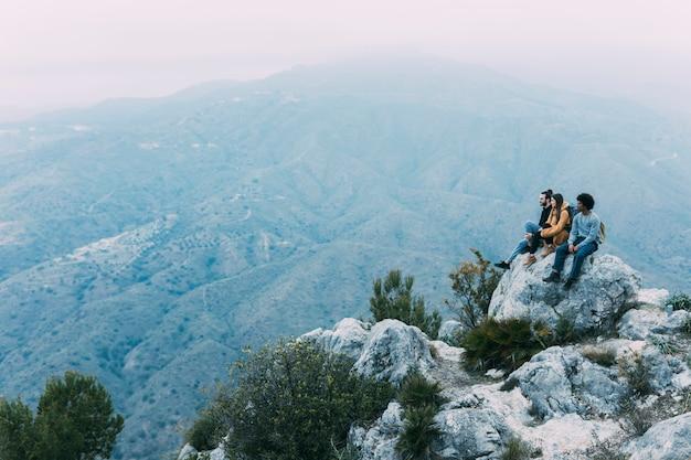 岩の上に座っているハイカーのグループ Premium写真