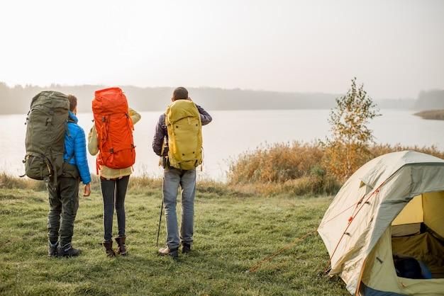 Группа туристов с красочными рюкзаками, стоящая на берегу озера возле кемпинга в туманную погоду