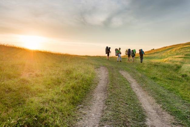 夕日の山の道でハイキング友達のグループ