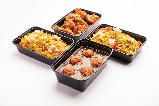 宅配のインド中華料理のグループは、プラスチックのパッケージ、シェズワンヌードル、チャーハン、チリチキン、満州料理、スープが入った容器または箱に入っています。