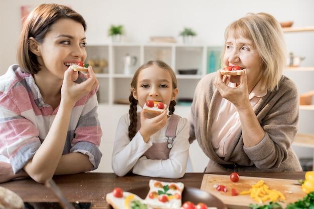 Группа голодных женщин ест домашние бутерброды с сыром и помидорами черри на кухне