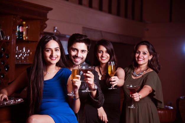 라운지 바에 앉아 음료 또는 칵테일을 마시고 새해, 생일 또는 성공을 축하하는 인도 아시아 친구 그룹
