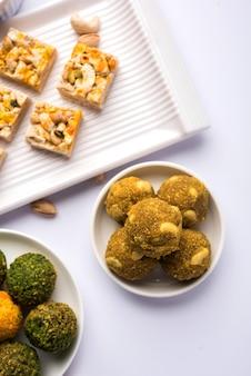 ドライフルーツラドゥー、カジュカトリ、ブルフィ、ガジャク、ティルパプディ、ラスマライ、グラブジャムンなどのインドのお祭りのお菓子のグループ。セレクティブフォーカス