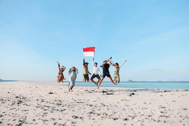 인도네시아 국기를 들고 있는 남자와 함께 해변에서 점프하는 인도네시아 사람들의 그룹