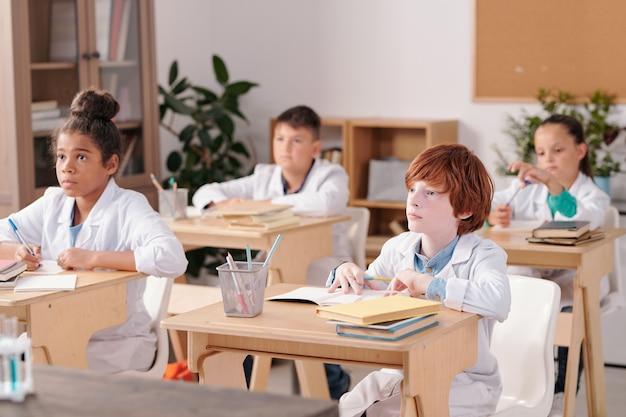 화학 수업에서 두 줄로 책상 옆에 앉아 교사를 바라보는 흰색 코트를 입은 다문화 초등학교 아이들