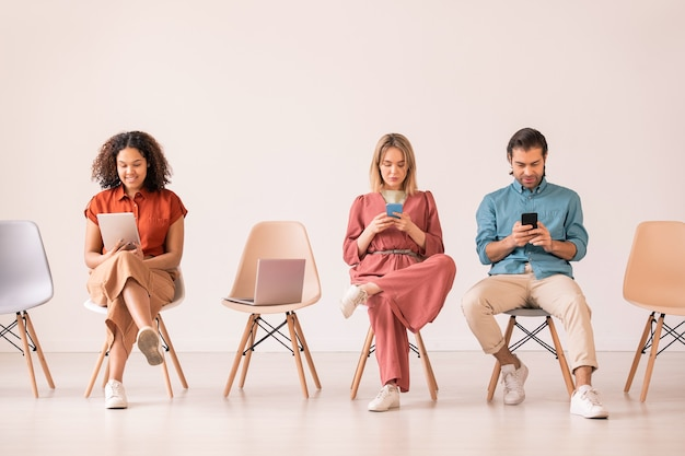 흰색 의자에 앉아 스마트 폰과 디지털 태블릿으로 스크롤하는 캐주얼웨어를 입은 밀레 니얼 세대의 그룹