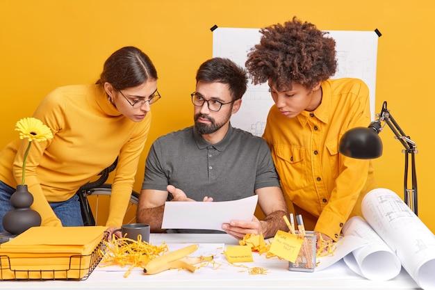 国際的な建築家のグループがエンジニアリングプロジェクトのアイデアについて話し合い、紙の黄色い壁に集中したデスクトップで一緒に作業プロセスを楽しんでいます。多様な同僚の旅館のオフィス。