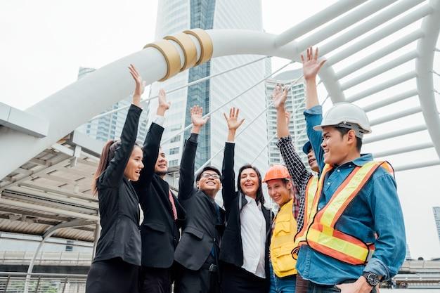 Группа международного делового и инженерного партнерства с поднятой рукой празднует успех