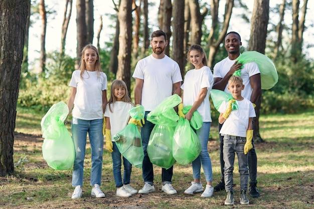 Группа международных волонтеров разного возраста с мешками для мусора после уборки территории.