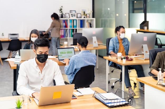 인종 간 비즈니스 작업자 팀 그룹은 새로운 일반 사무실에서 얼굴 보호 마스크를 착용합니다.